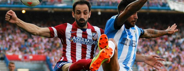 Atletico Madrid's Juanfran Torres (L) and Malaga's Samual Garcia fight for the ball during their Spanish first division soccer match at Vicente Calderon stadium in Madrid May 11, 2014. REUTERS/Sergio Perez (SPAIN - Tags: SPORT SOCCER) SLOWA KLUCZOWE: :rel:d:bm:GF2EA5B1CYA02