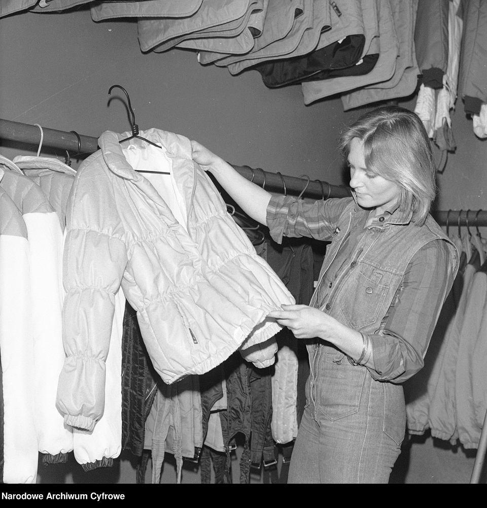 Wnętrze sklepu. Kobieta ogląda kurtkę firmy 'Mazziotti' w Warszawie, 1982 r.
