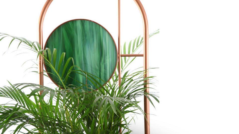 Kwietnik Hula z lustrem oraz długimi metalowymi elementami, które podtrzymują pnącza.