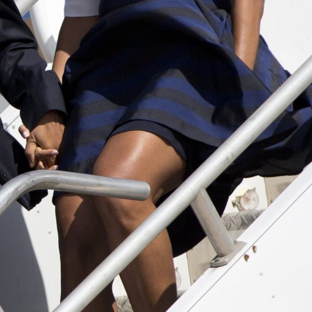 First lady Michelle Obama's dress is caught in the wind as she and President Barack Obama arrive at Austin-Bergstrom International Airport on Air Force One, Thursday, April 10, 2014, in Austin, Texas, en route to the LBJ Presidential Library to attend a Civil Rights Summit to commemorate the 50th anniversary of the signing of the Civil Rights Act. (AP Photo/Carolyn Kaster)