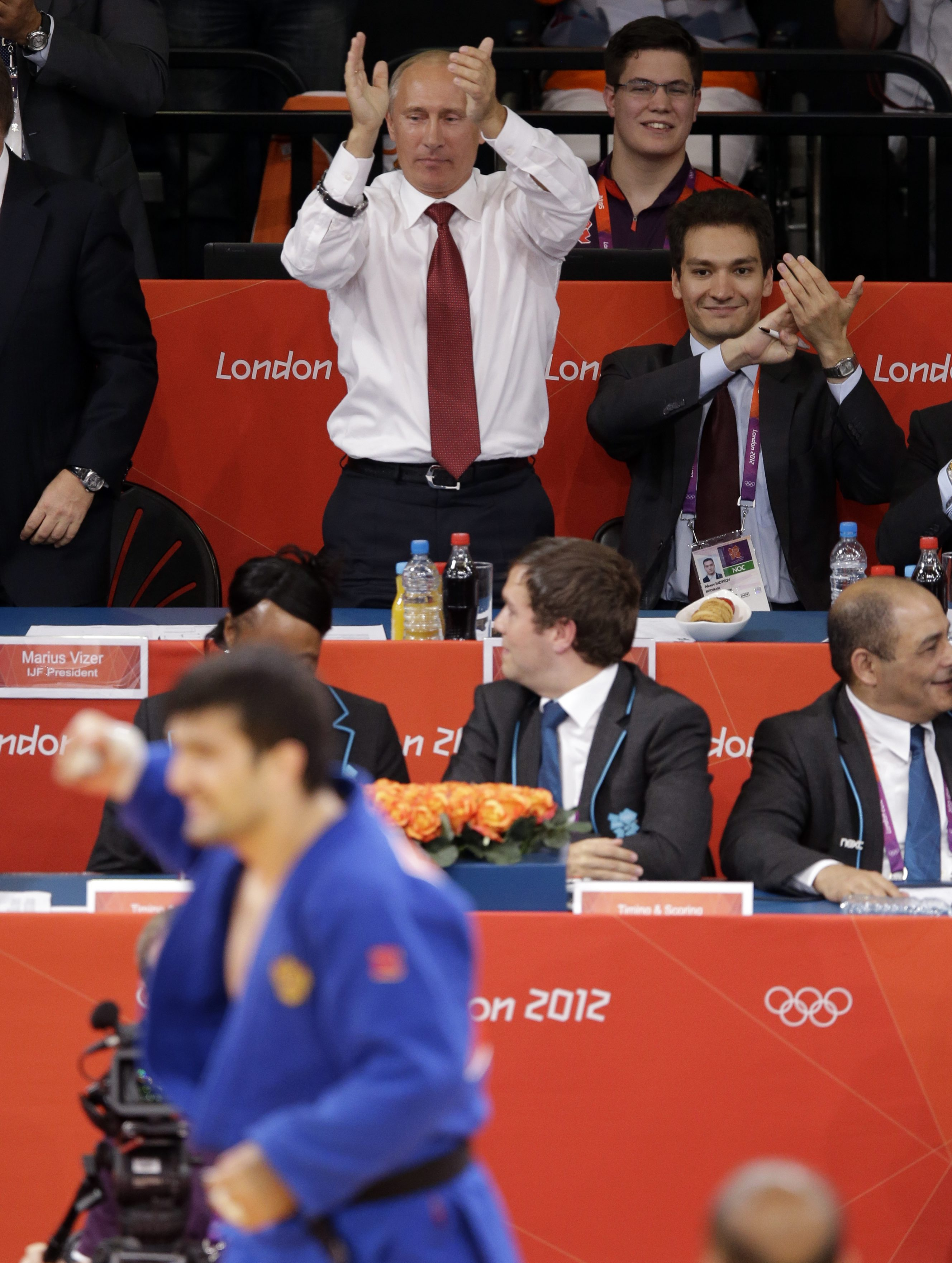 Russian President Vladimir Putin applauds Tagir Khaibulaev of Russia after he beat Tuvshinbayar Naidan of Mongolia  to win the gold medal during the men's 100-kg judo competition at the 2012 Summer Olympics, Thursday, Aug. 2, 2012, in London. (AP Photo/Ng Han Guan)