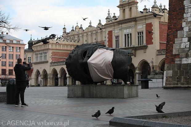 Rzeźba Igora Mitoraja na Rynku Głównym w Krakowie ubrana w maskę .