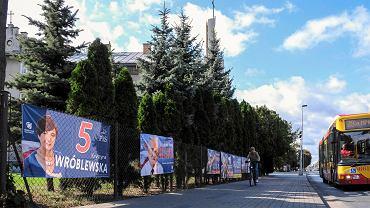 Rzeszów , ul. Dąbrowskiego. Plakaty wyborcze kandydatów PiS na ogrodzeniu budynku sąsiadującego z kościołem pw Matki Boskiej Saletyńskiej, który należy do Saletynów .