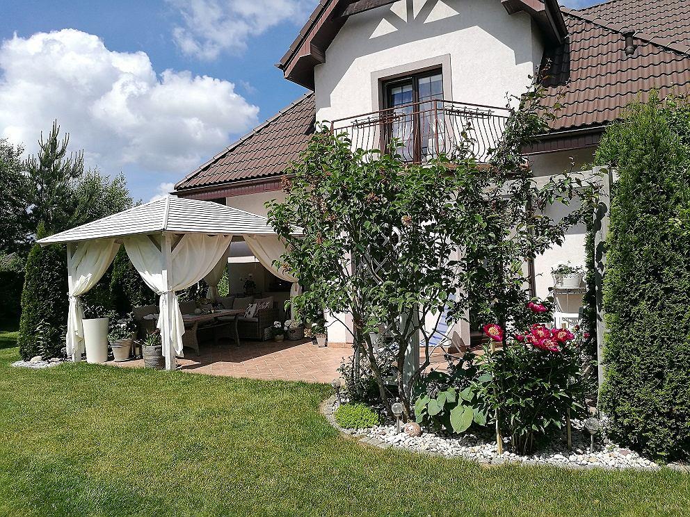 Dom, podobnie jak wewnątrz, z zewnątrz jest biały. Latem wygląda najpiękniej - cały tonie w zieleni.