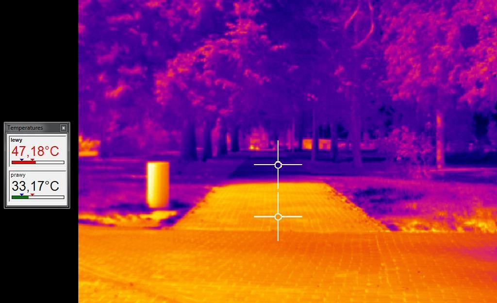 Obraz z kamery termowizyjnej. Osłonięta część chodnika ma temperaturę 33 stopni Celsjusza, nasłoneczniona - 47 stopni
