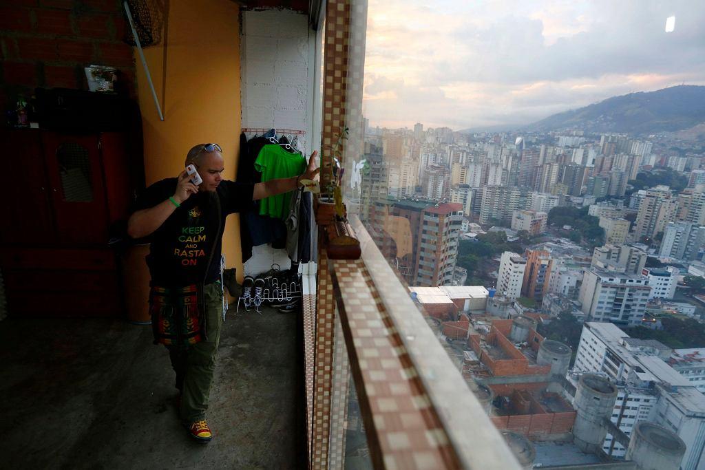 Nicolas Alvarez rozmawia przez telefon, patrząc przez okno na 27. piętrze Wieży Dawida