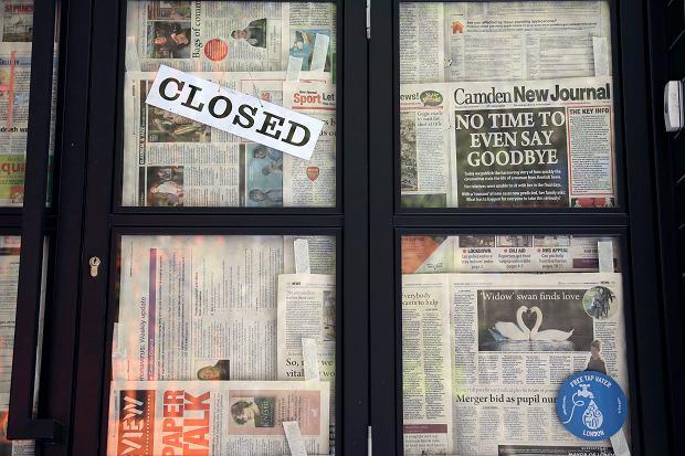 Według ostatniego raportu Brookings Institution jedna na pięć gazet lokalnych w USA od 2004 r. zniknęła z rynku prasy. Na zdjęciu: pandemia koronawirusa. Drzwi zamkniętej restauracji zasłonięte stronami lokalnej prasy ('Camden New Journal'). Londyn, 20 kwietnia 2020