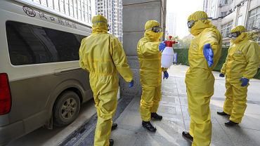 Pracownicy domu pogrzebowego z Wuhan podczas dezynfekcji po pochówku ofiar koronawirusa