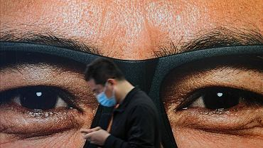 Chiny. Przechodzień w masce przed billboardem przedstawiającym mężczyznę w okularach