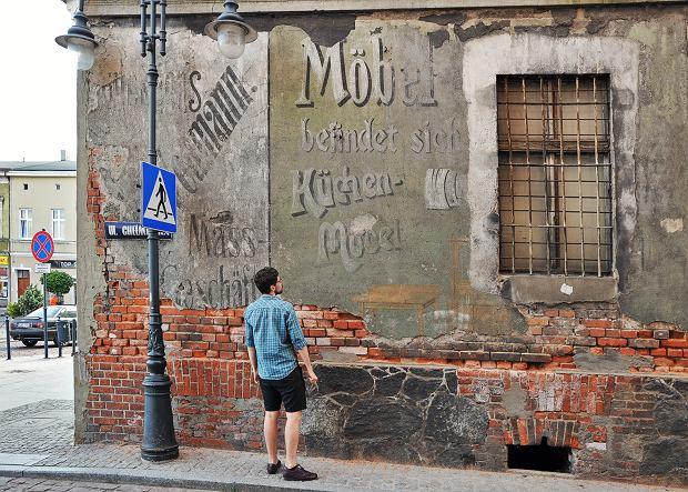 Dawne reklamy wielkopowierzchniowe w Wąbrzeźnie w woj. kujawsko-pomorskim. Na zdjęciu jest Kamil Snochowski, pasjonat napisów z Torunia