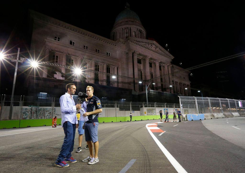 Sebastian Vettel udziela wywiadu przy interesującym elemencie architektonicznym na zakręcie nr 10.