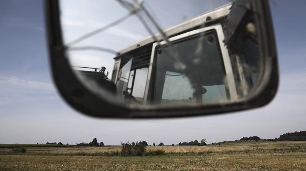 A tractor owned by a local farmer is seen reflected in a broken mirror with the Belarus border visible in the distance on 14 August, 2021 in Zubrzyca Wielka, Poland.