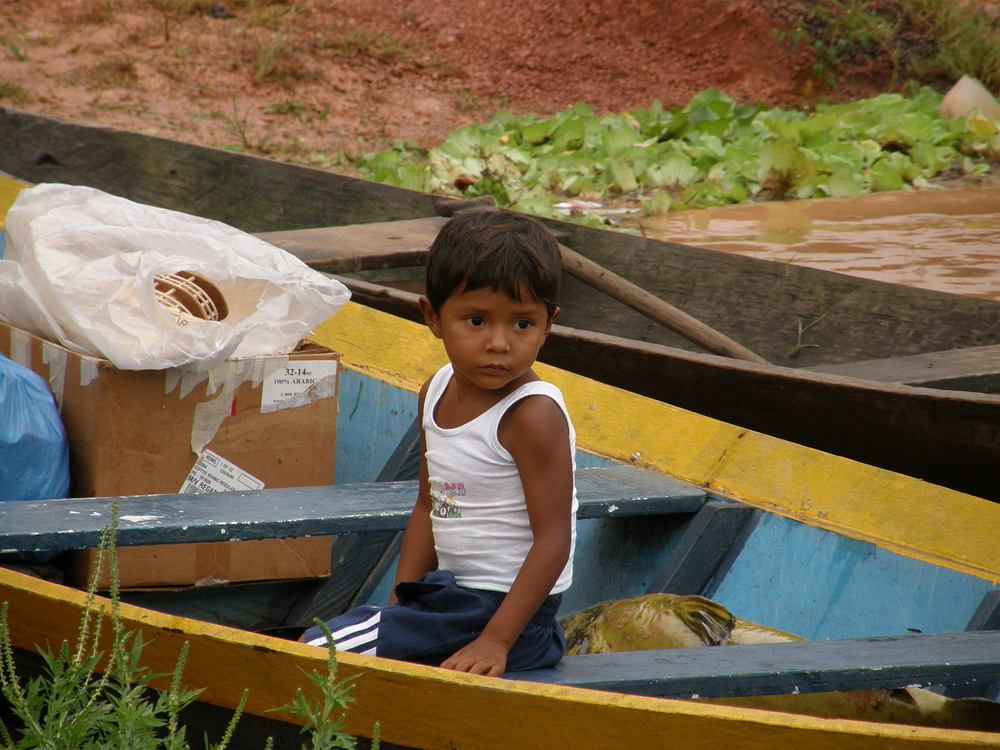 Amazonka, Amazonia, Ameryka Południowa - BOCA DE VALERIA, Brazylia: Mały Indianin w swoim canoe szykuje się do powrotu do domu po dniu spędzonym z rodziną na targowisku