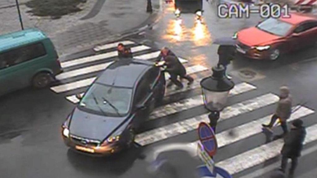 Strażnicy miejscy pchają samochód posła PiS Bartłomieja Wróblewskiego
