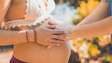 Para trzyma dłonie na brzuchu ciężarnej kobiety. Zdjęcie ilustracyjne