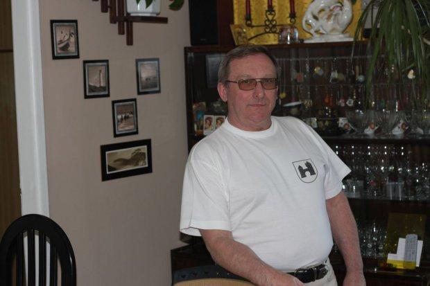 Dariusz Olszewicz w swoim mieszkaniu, w tle regał, który stał tu także, gdy kręcono