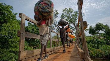 Uchodźcy z Sudanu przekraczają granicę z Ugandą.