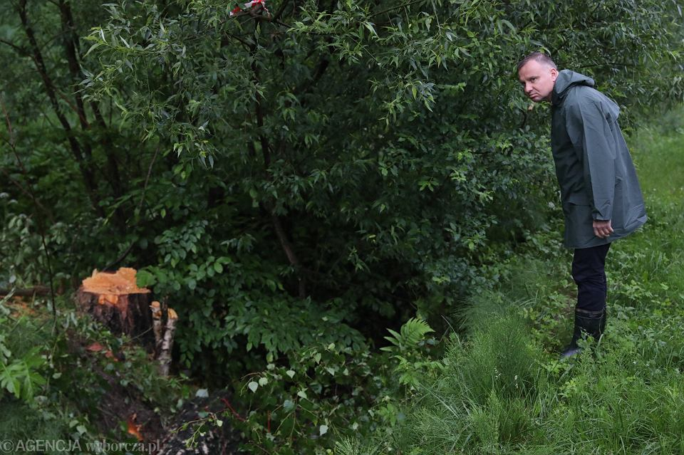 Andrzej Duda, w stosownym stroju, pochyla się z troską nad losem podtopionych. Gospodarska wizyta prezydenta RP - po nocnych, intensywnych opadach w Krzesławicach, 21 czerwca 2020