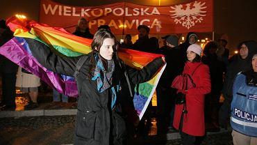 Obchody rocznicy wprowadzenia stanu wojennego w Polsce. Kobieta próbuje zasłonić flagą LGBT flagę ONR-u.