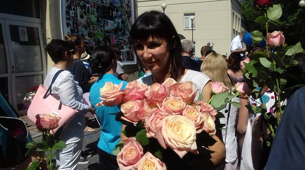 Dr Marzena Dębka rozdaje kwiaty, które otrzymała