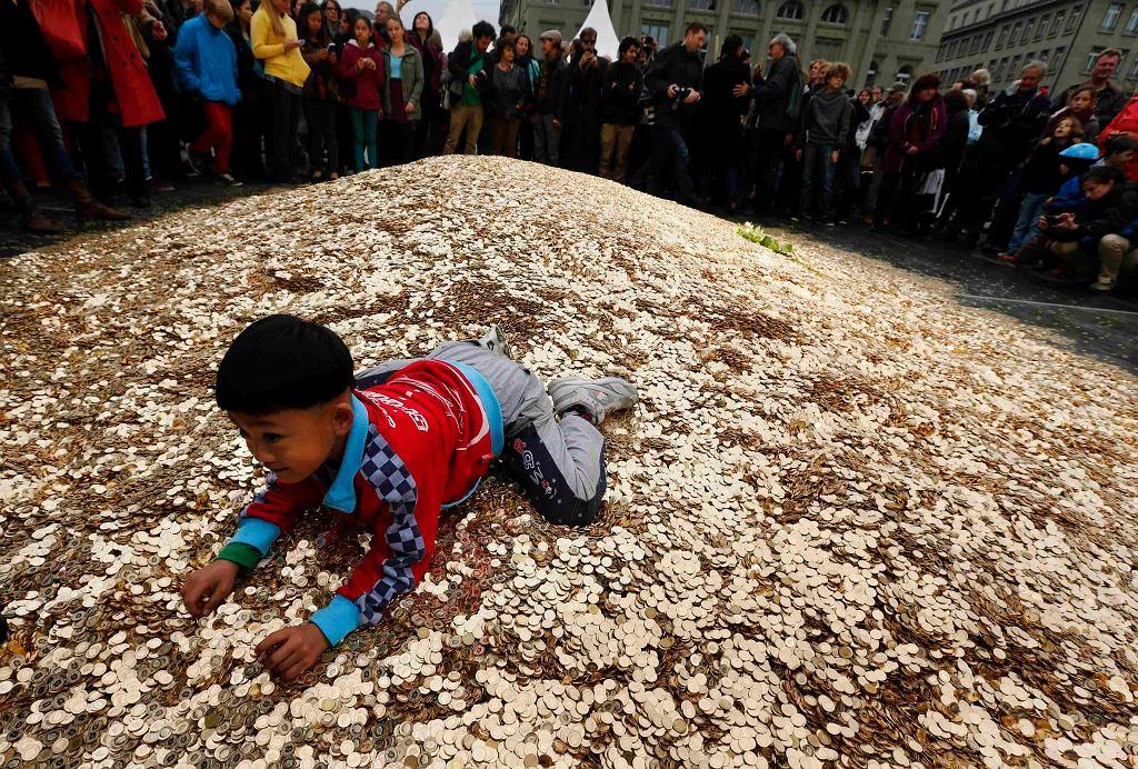 Dziecko bawi się w monetach wysypanych przed siedzibą szwajcarskiego parlamentu. Wysypali je orgniaztorzy zbiórki podpisów pod referendum