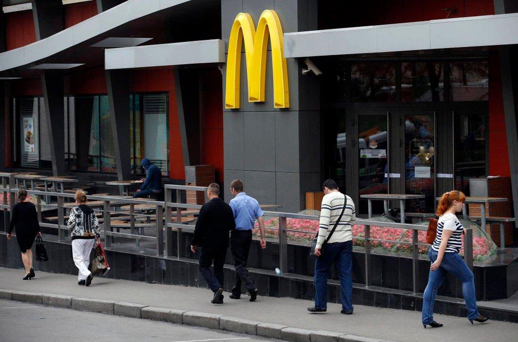 Ludzie przechodzą koło zamkniętego baru Mcdonald's w Moskwie