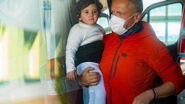 Uchodźcy. 'Medycy na granicy' pomogli trójce migrantów, w tym dwuletniej dziewczynce. Dr Paweł Podkościelny z dziewczynką na rękach