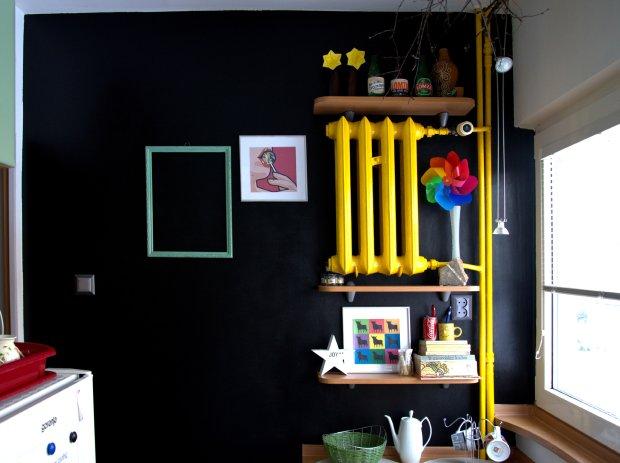 Odmieniona ściana. Całość została pokryta czarną farbą tablicową. Grzejnik i rury zostały pomalowane w kontrastowym, żółtym kolorze. Dzięi niemu ściana nabrała wyrazu.