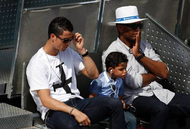 ATTENTION EDITORS: SPANISH LAW REQUIRES THAT THE FACES OF MINORS ARE MASKED IN PUBLICATIONS WITHIN SPAIN    Real Madrid's Cristiano Ronaldo (L) and his son Cristiano Ronaldo Jr (C) attend the Nadal-Nieminen match at the Madrid Open tennis tournament May 8, 2014. REUTERS/Susana Vera (SPAIN - Tags: SPORT TENNIS SOCCER) SLOWA KLUCZOWE: :rel:d:bm:GF2EA5817TV01