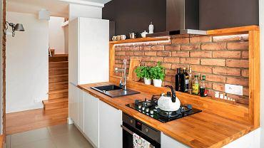DOM. Cegła na ścianie nad kuchennym blatem została ujęta w dębową ramę, która służy jako półka. Przy ścianie zainstalowano ledowe oświetlenie.