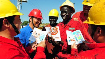 Chińscy i sudańscy pracownicy  firmy wydobywającej ropę naftową czytają książki z kreskówkami na polu naftowym w południowym  Sudanie