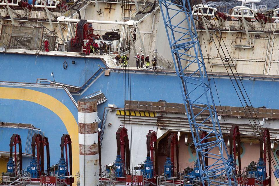 Po ustawieniu statku do pionu, wypełnione wodą kesony zostaną przymocowane też z drugiej strony wraku, żeby ustabilizować statek. Później, woda z kesonów zostanie wypompowana, a statek - odholowany do miejsca, gdzie zostanie zniszczony. Na zdjęciu: pracownicy na górnym pokładzie Costy Concordii