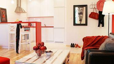 Prosta zabudowa kuchenna wtapia się w przestrzeń salonu. Elementem oddzielającym dwie części pomieszczenia jest czerwony barek. Stanowi od jednocześnie miejsce do spożywania posiłków.