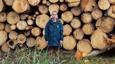 Jan Kapela na tle stosu wyciętych drzew z Puszczy Białowieskiej