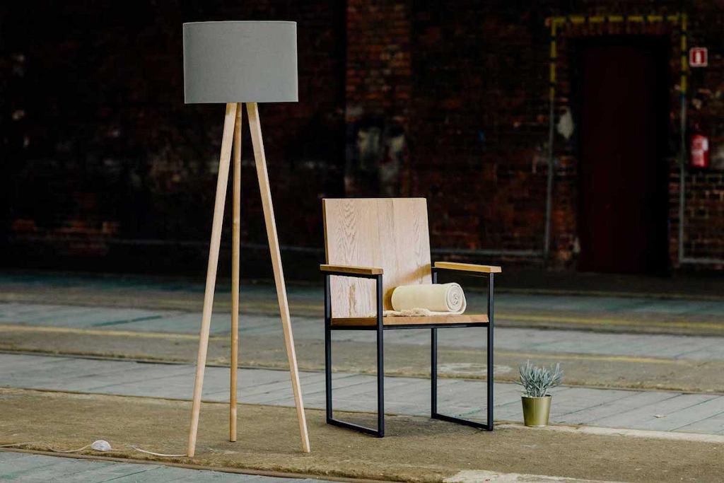 Krzesło Czerteż z siedziskiem i oparciem z litego drewna oraz stalową konstrukcją.