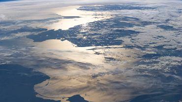 """Na stronie """"Earth Observatory"""" NASA codziennie dzieli się najciekawszymi fotografiami Ziemi, jakie z orbity nadsyłają satelity lub załoga stacji orbitalnej. Pokazują one zmiany, zarówno w skali globalnej, jak i lokalnej. Widać, jak niektóre regiony pustynnieją na skutek ocieplenia klimatu, inne są transformowane przez rosnącą rzeszę ludzi lub kataklizmy. Ale widać też jeszcze jedno: z wysokości kilkuset kilometrów świat jest po prostu piękny. Na zdjęciu: Bałtyk i zarys północnej Polski z Półwyspem Helskim w promieniach zachodzącego Słońca (zdjęcie wykonane ze stacji orbitalnej ISS)"""