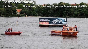 Baner z reklamą samochodu ustawiony na pływającej platformie na Szlaku Wielkich Jezior Mazurskich