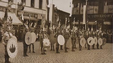 Wszystko zaczęło się 8 sierpnia 1917 roku. O godz. 20 w salce parafialnej przy kościele Św. Trójcy zebrało się ok. 40 młodych ludzi, by dowiedzieć się szczegółów dotyczących utworzenia drużyny w Bydgoszczy. Organizował ją Jan Wierzejewski. Wyznaczył pięć zastępów. Patronem pierwszej w mieście drużyny skautowej został Stanisław Staszic.  Umundurowali się we własnym zakresie, co nie było łatwe, bo przecież trwała jeszcze wojna. We wrześniu pokazali się oficjalnie po raz pierwszy: uroczyście witali arcybiskupa Edmunda Dalbora, prymasa Polski.   Historię bydgoskiego harcerstwa dokumentują harcerze-pasjonaci. Prezentujemy kilkadziesiąt spośród ok. 700 fotografii, które znajdą się w albumie 'Harcerska wędrówka przez stulecie. Sto lat bydgoskiego harcerstwa w fotografii'. Wydawnictwo ma ukazać się pod koniec roku. Pracuje nad nim Zespół Historyczny Okręgu Kujawsko-Pomorskiego Związku Harcerstwa Rzeczypospolitej. - Za nami osiem miesięcy nieustannej, ciężkiej pracy - opowiada hm. Piotr Grądziel. - Zrobiliśmy kwerendę w bydgoskich i toruńskich muzeach, archiwach, bibliotekach. Spotkaliśmy się z pasjonatami, sympatykami harcerstwa, ale też z ostatnimi z żyjących przedwojennych harcerzy. Niektórzy zaskakiwali zdumiewająco dobrą pamięcią. Z nazwiska potrafili wymienić kilkanaście osób na zdjęciu sprzed 70 lat. Chcemy, by album przemawiał głównie obrazem. Ale dbamy o to, by każdą z fotografii jak najbardziej szczegółowo opisać.  Wraz z Grądzielem nad albumem pracują: hm. Bogusława Pasieka - Butkiewicz, hm. Janusz Pruski, hm. Michał Butkiewicz, pwd. Robert Sawicki oraz z ramienia Związku Harcerstwa Polskiego hm. Piotr Nawrocki. Zdjęcia w albumie ułożono chronologicznie. Pierwsze dwa rozdziały pokażą bydgoskie harcerstwo z okresu zaborów i międzywojnia. Prezentujemy 29 spośród kilkuset zgromadzonych przez autorów albumu zdjęć z tego okresu. Na zdjęciu: Patriotyczna manifestacja harcerzy na Starym Rynku. W strojach husarii 'wilczęta' 12 Bydgoskiej Drużyny Harcerzy im. ks. Józefa Po