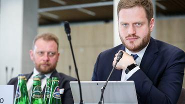 Na pierwszym planie b. wiceminister zdrowia Janusz Cieszyński, w tle na zdjęciu b. minister zdrowia Łukasz Szumowski
