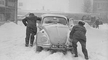 Mężczyźni pchają samochód Volkswagen Garbus. Z lewej budynek przy ul. Malczewskiego 48/50, 30.01.1979