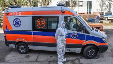 Karetka i ratownik w stroju ochronnym w związku z koronawirusem