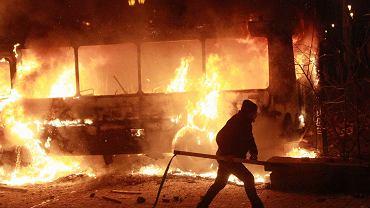 Jeden z uczestników starć, w tle płonący samochód milicji