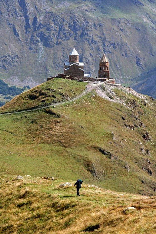 Kazbegi to miejsce jak z bajki: monastyr Cminda Sameba na tle białych szczytów wielkiego Kaukazu / fot. Shutterstock