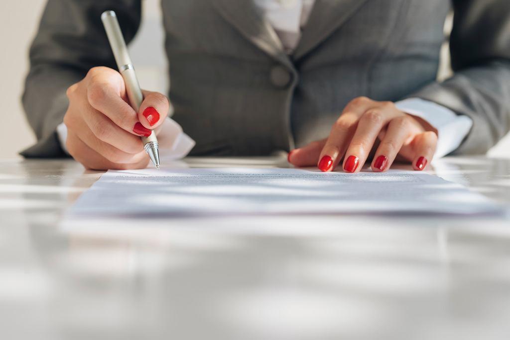 Close-up of female manicured hands signing a document podpisywane dokumenty pracownik biurowy prawnik
