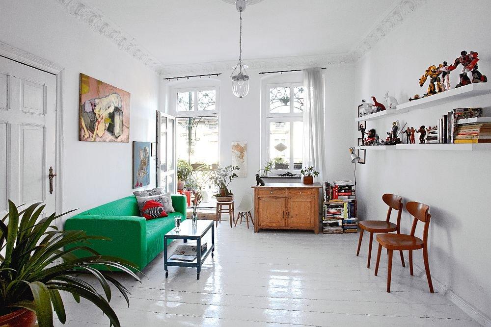 W salonie zachowały się oryginalne sztukaterie. Zieloną kanapę (IKEA) zestawiono z niebieskim stolikiem na kółkach. Kolekcja starych krzeseł wizualnie podkreśla galerię przeróżnych zabawek Małgorzaty. Lampa stylizowana IKEA, obraz olejny Karoliny.