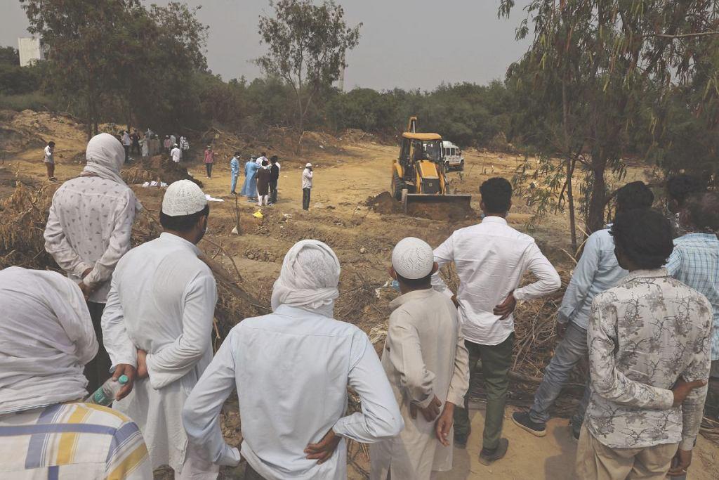 WHO ostrzega, że pandemia przyspiesza. Na zdjęciu pochówek zmarłych na covid-19 w New Delhi w Indiach