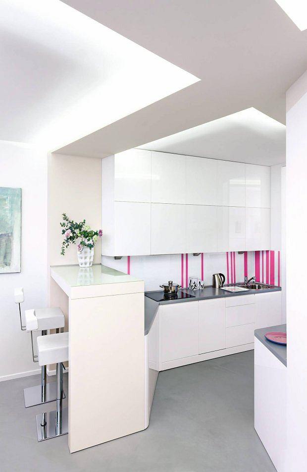 SZKŁO + NAKLEJKI. Kuchnia utrzymana w bieli i szarości mogłaby się wydawać zbyt sterylna i monotonna. Zapobiegły temu różowe naklejki, którymi ozdobiona tafle białego szkła lacobel na ścianie. Naklejki nie utrudniają czyszczenia ściany, a jak się znudzą, można je łatwo odkleić.