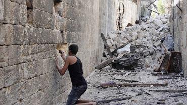 Zniszczona stara część Aleppo. Syryjski bojownik wykuwa otwór pod karabin dla strzelca wyborowego