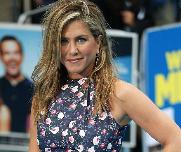 "Actress Jennifer Aniston poses for photographers as she arrives for the UK premiere of ""We're the Millers"" in Leicester Square in central London August 14, 2013. REUTERS/Andrew Winning  (BRITAIN - Tags: ENTERTAINMENT SOCIETY)"