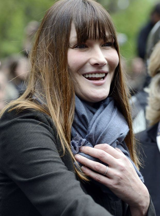 Carla Bruni-Sarkozy, wife of France's incumbent President and right-wing ruling party Union for a Popular Movement (UMP) candidate for the French 2012 presidential election Nicolas Sarkozy, leaves the polling station after voting with her husband, on May 6, 2012 for the election second round.                   AFP PHOTO / ERIC FEFERBERG